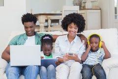 Lycklig familj som använder teknologier på soffan fotografering för bildbyråer