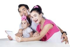 Lycklig familj som använder den digitala minnestavlan Arkivfoto