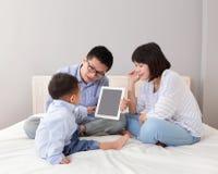 Lycklig familj som använder tabletPC Arkivfoto