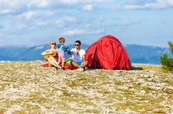 Lycklig familj som campar i berg Arkivbild