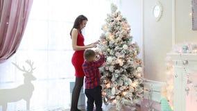 Lycklig familj som dekorerar en julgran i en inre för ` s för nytt år lager videofilmer
