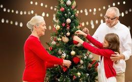 Lycklig familj som dekorerar julgranen Arkivfoto