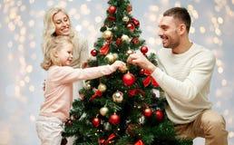 Lycklig familj som dekorerar julgranen Fotografering för Bildbyråer