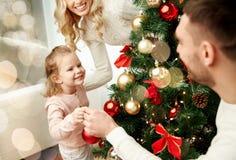 Lycklig familj som dekorerar julgranen Royaltyfri Foto