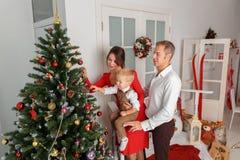 Lycklig familj som dekorerar julgranen Ferier och gyckel för nytt år Fotografering för Bildbyråer
