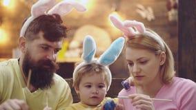 Lycklig familj som dekorerar påskägg som sitter på tabellen, slut upp Närbildstående av den gladlynta familjen på helgdagsaftonen lager videofilmer
