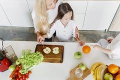 Lycklig familj som förbereder bästa sikt för sunt frukosthemkök royaltyfria foton