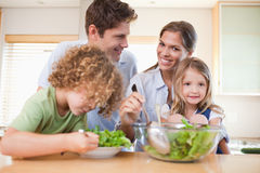 Lycklig familj som förbereder en sallad Fotografering för Bildbyråer