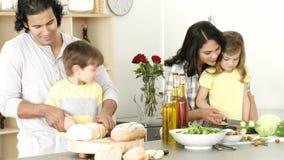Lycklig familj som förbereder ett mål i köket arkivfilmer