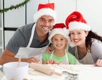 Lycklig familj som förbereder julkakor Royaltyfria Bilder