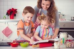 Lycklig familj som förbereder kakor för julhelgdagsafton arkivbilder