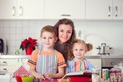 Lycklig familj som förbereder kakor för julhelgdagsafton fotografering för bildbyråer