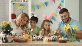 Lycklig familj som förbereder sig för påsk och målar påskägg stock video