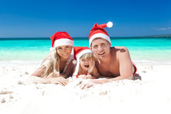 Lycklig familj som firar jul på stranden Royaltyfria Bilder