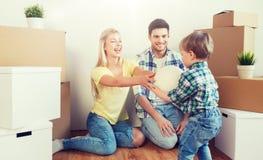 Lycklig familj som flyttar sig till det nya hemmet och spelar bollen Royaltyfria Foton