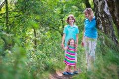 Lycklig familj som fotvandrar i ett sörjaträ Royaltyfria Foton
