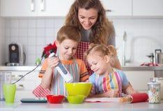Lycklig familj som förbereder kakor för julhelgdagsafton Arkivbild