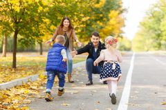 Lycklig familj som går i parkera i höst arkivfoton