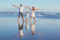 Lycklig familj som går med gyckel på solnedgånghavsstranden Arkivfoto