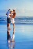 Lycklig familj som går med gyckel på solnedgånghavsstranden Fotografering för Bildbyråer