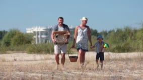 Lycklig familj som går på pinic till stranden lager videofilmer