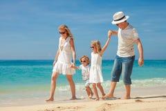 Lycklig familj som går på stranden på dagtiden Arkivfoton