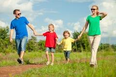 Lycklig familj som går på vägen Arkivbild