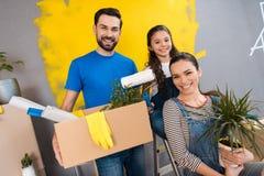 Lycklig familj som gör reparationer i det till salu huset Begrepp av att sälja för hus royaltyfria foton