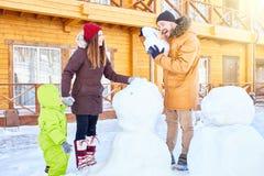 Lycklig familj som gör snowmanen royaltyfri fotografi