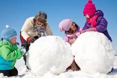 Lycklig familj som gör snowmanen Royaltyfri Foto