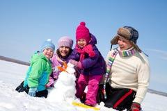 Lycklig familj som gör snowmanen Arkivfoto