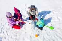Lycklig familj som gör snowmanen Arkivbild