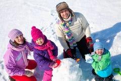Lycklig familj som gör snowmanen Arkivbilder