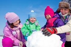 Lycklig familj som gör snowmanen Royaltyfria Bilder