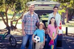 Lycklig familj som går för campa i parkera Royaltyfri Bild