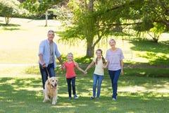 Lycklig familj som går i parkera med deras hund Arkivfoton