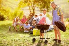 Lycklig familj som grillar kött Arkivfoton