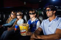 Lycklig familj som håller ögonen på filmen 3D Arkivbild