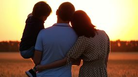 Lycklig familj som håller ögonen på solnedgången som står i ett vetefält En man som rymmer ett barn i hans armar En kvinna kramar stock video