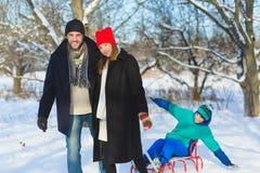 Lycklig familj som har den utomhus- roliga snöig skogsmarken Arkivbild
