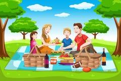 Lycklig familj som har en picknick Fotografering för Bildbyråer