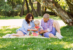 Lycklig familj som har en picknick i parkera som äter en vattenmelon Royaltyfri Bild