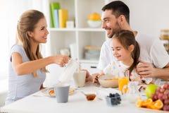 Lycklig familj som har frukosten hemma arkivfoto