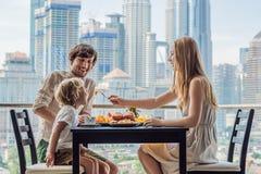 Lycklig familj som har frukosten på balkongen Frukosttabell med kaffefrukt och bröd som är croisant på en balkong mot arkivbilder