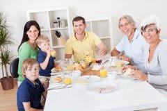 Lycklig familj som har frukosten tillsammans Arkivbilder
