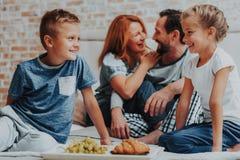 Lycklig familj som har frukosten tillsammans i morgon arkivbild