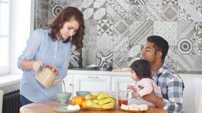 Lycklig familj som har frukosten tillsammans i morgonen hemma i köket arkivfilmer