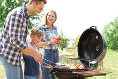 Lycklig familj som har grillfesten med gallret utomhus arkivfoton