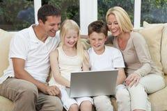 Lycklig familj som har gyckel genom att använda en dator hemma Arkivfoton