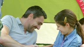 Lycklig familj som har gyckel i deras tält på en campa tur lager videofilmer